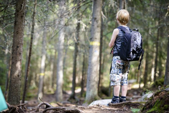 Poika metsässä mietteliäänä