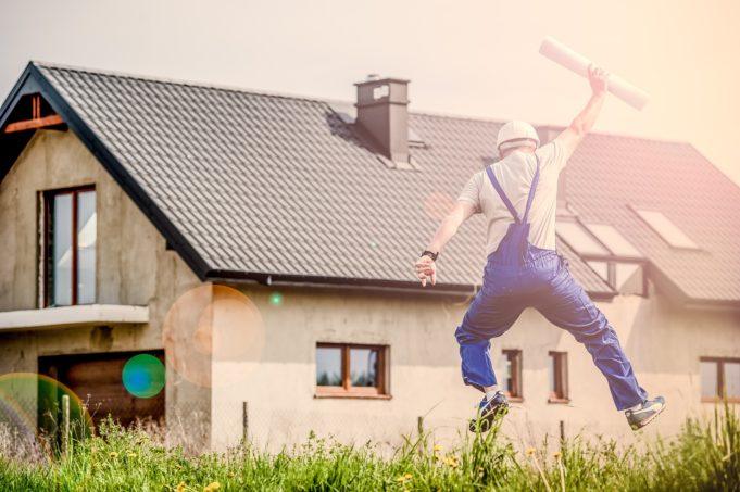 työmies hyppää ilmaan ja pitää kädessään rakennuspiirrustusta