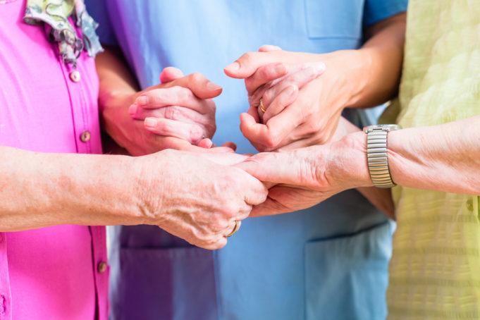 ikäihmisten ja hoitajan kädet