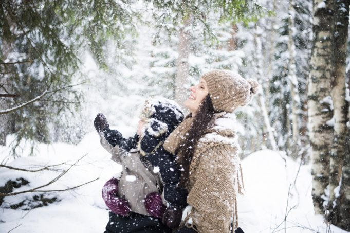 aikuinen ja lapset lumisateessa