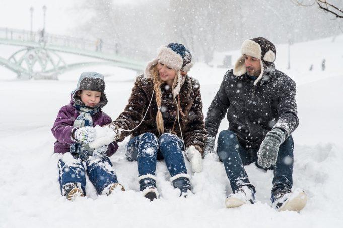 Lapsi ja kaksi aikuista istuvat lumessa.