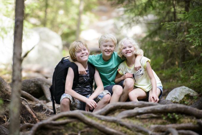 Kolme iloista lasta metsässä.